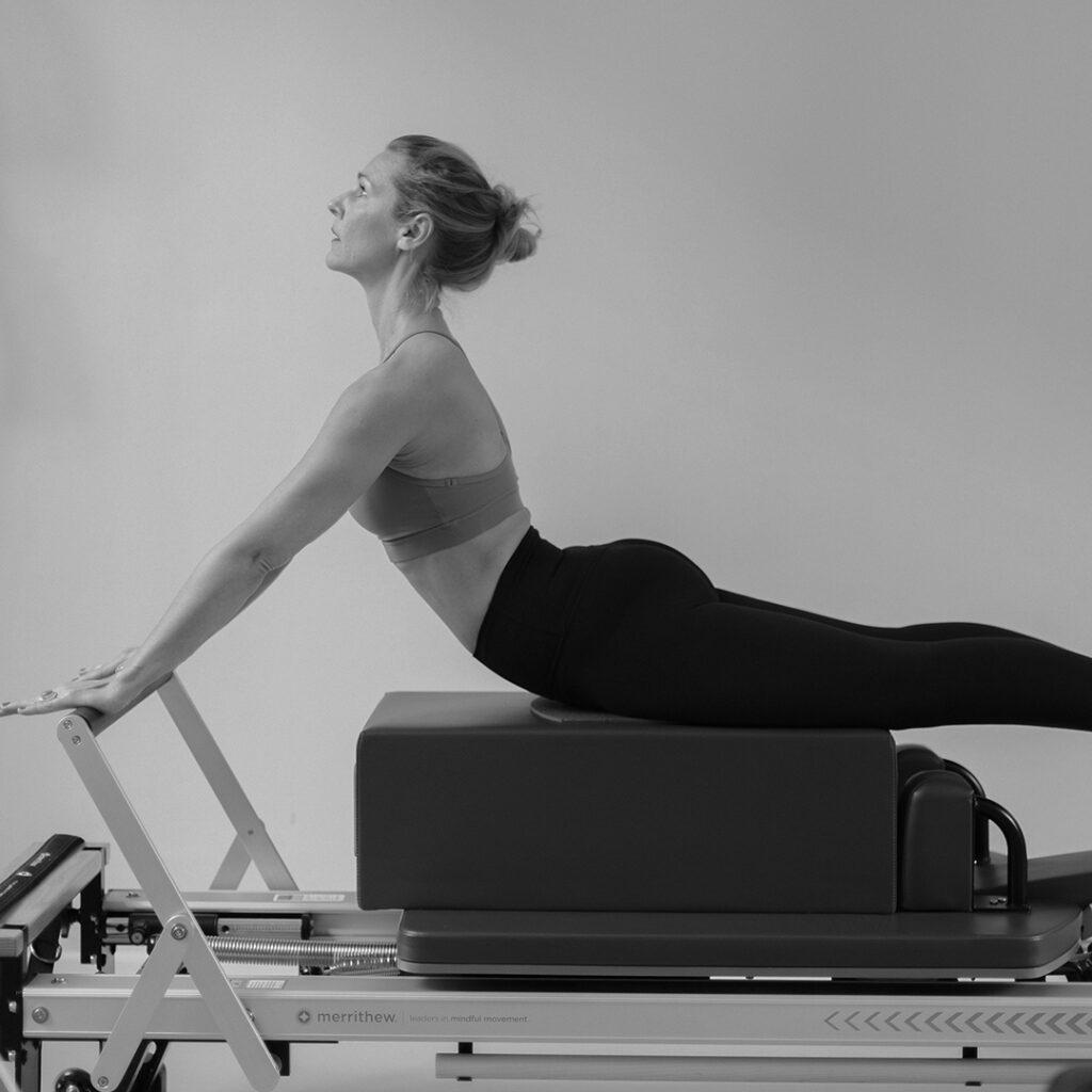 Eine Frau trainiert die Pilates Übung Swan auf dem Pilates Reformer im Studio.